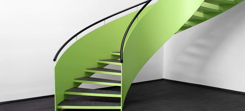 Sondertreppe aus Stahl mit grüner Lackierung und Schieferfliesen. Auf den Brüstungswangen ist ein Holzhandlauf angebracht.