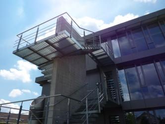 Stahlaußentreppe in Künzelsau. Kragarmstufen an einer Sichtbetonwand befestigt